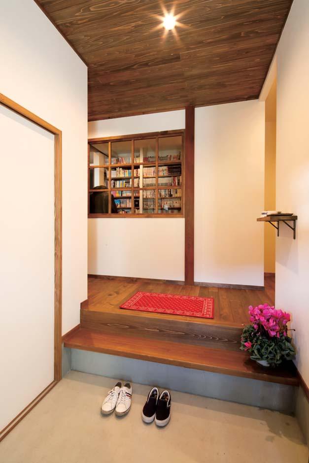 玄関引き戸を開けると、モルタルの土間の向こうに無垢ヒノキの床と杉板の天井の廊下につながる。正面の廊下は昔の小学校の図書室を思わせる格子窓でニュアンスを出した
