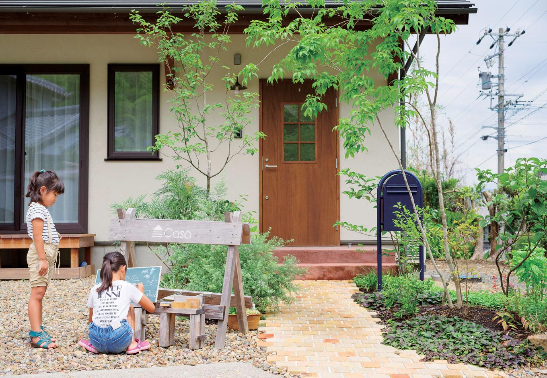 Casa(カーサ)【趣味、自然素材、インテリア】塗り壁と木製ドアの組み合わせが目を引く外観。玄関周りの植栽まで『カーサ』の視点でプロデュースされ、レンガの小道とのバランスもいい