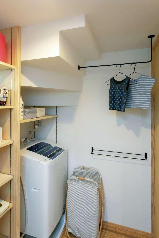階段下を活かしたランドリースペース。洗濯機の近くにあるアイアンのフックが便利そう