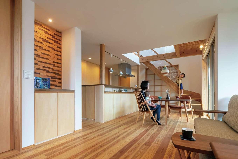あだちの家。足立建築【子育て、収納力、間取り】リビングの天井は低めに抑えて落ち着きと寛ぎ感を創出。キッチン周りにはいたるところに収納を配置しつつ、コンパクトな動線を叶えている。木の端材を組み合わせた壁面のウッドパネルがシンプルな空間のアクセントに