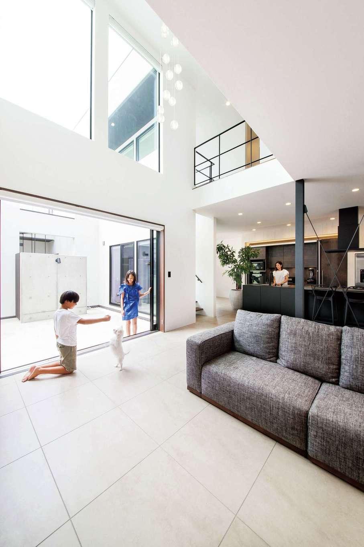 寿建設【高級住宅、間取り、屋上バルコニー】圧倒的なスケールを誇る吹抜けのLDKは40畳。白を基調とした空間に黒い柱、キッチン、手すりが映えるモダンな空間がカッコイイ。600角の大きなタイルがさらなる高級感を演出