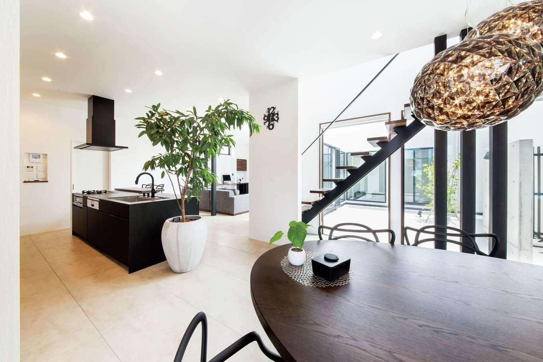 寿建設【高級住宅、間取り、屋上バルコニー】中庭からたっぷりの光と風を取り込むLDK。つながりを持たせながら、ゆるやかにゾーニングされた空間で、ブラックマットのアイランドキッチンとリビング階段がオブジェのような存在感を放っている