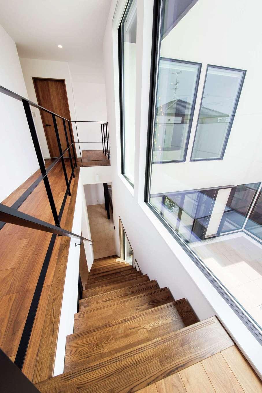寿建設【高級住宅、間取り、屋上バルコニー】吹抜けのリビング階段。大きなピクチャーウィンドウから燦々と光が降り注ぐ。キッチンから2階にいる子どもたちの気配が分かるので奥さまも安心