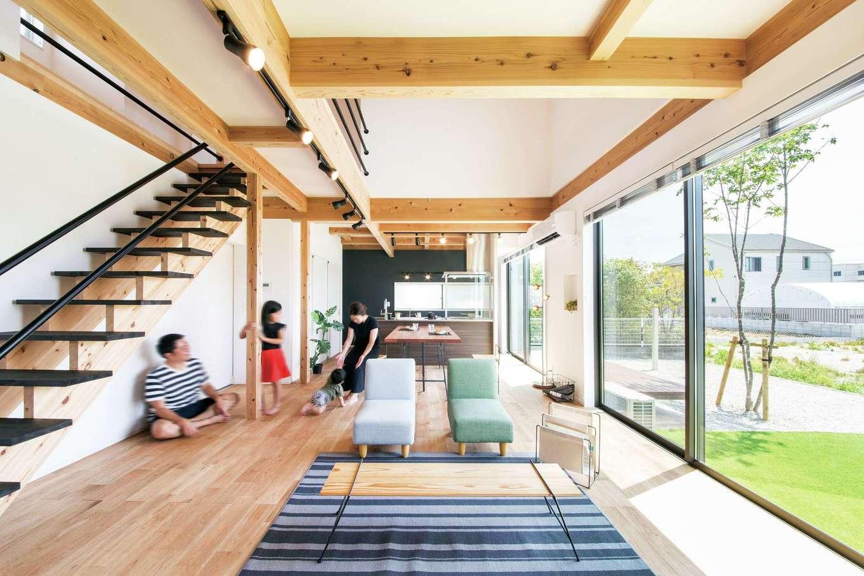 住たくeco工房【子育て、自然素材、間取り】開放感あふれる吹抜けのLDKは24.6畳の大空間。大きな窓から四季折々の庭の景色を楽しむことができる。肌触りのいい床は浮造りの天竜杉で、経年変化も楽しみ