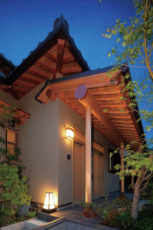 照明に映える玄関庇。丸太の垂木と丸太の桁(垂木を支える横架材)がきっちりと組み合わさるように手仕事で細かい加工を施してある