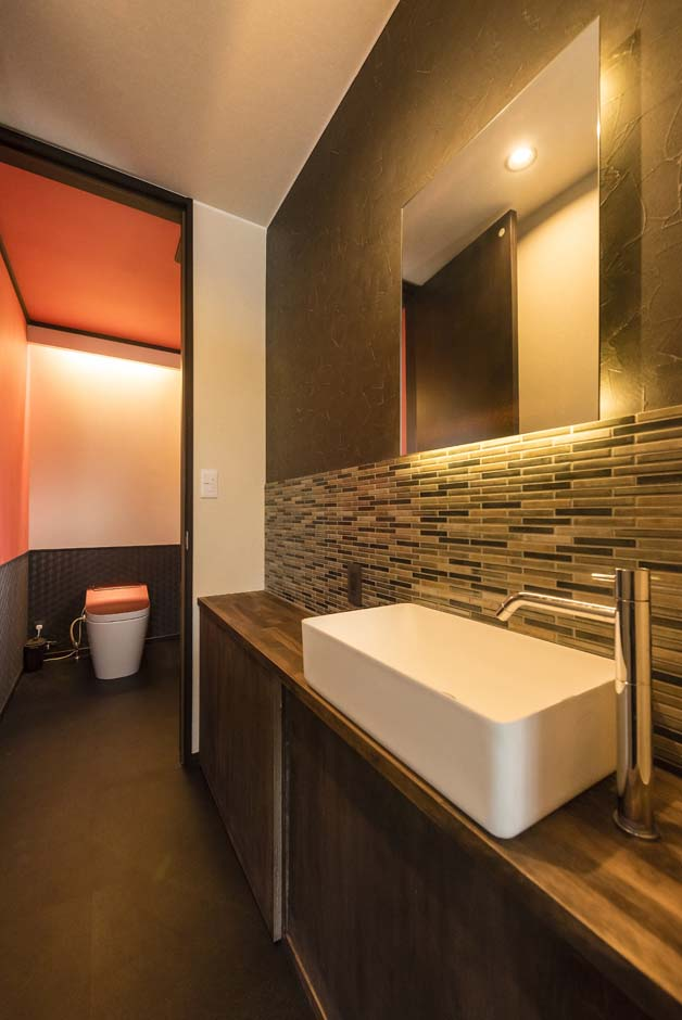 アトリエサクラ【デザイン住宅、間取り、ガレージ】モダンなタイル使いとの洗面台。トイレの天井にはアクセントカラーのオレンジのクロスを用いた