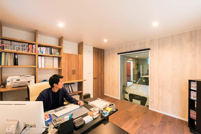 アトリエサクラ【デザイン住宅、間取り、ガレージ】事務所のフィックス窓からは、ガレージの愛車をいつでも眺められる。デスクまわりの書類棚は使いやすさを考慮して造作に