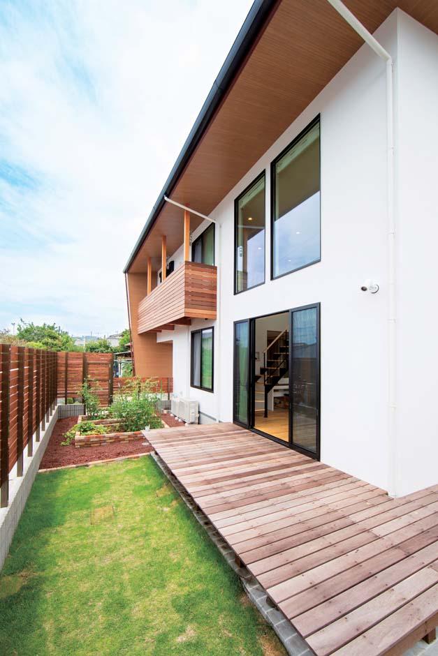 TENアーキテクツ 一級建築士事務所【子育て、間取り、建築家】深く伸ばした軒が夏の直射を遮り、冬は光を室内の奥まで届ける。L字型のウッドデッキと家庭菜園が子どもの創造力を育む