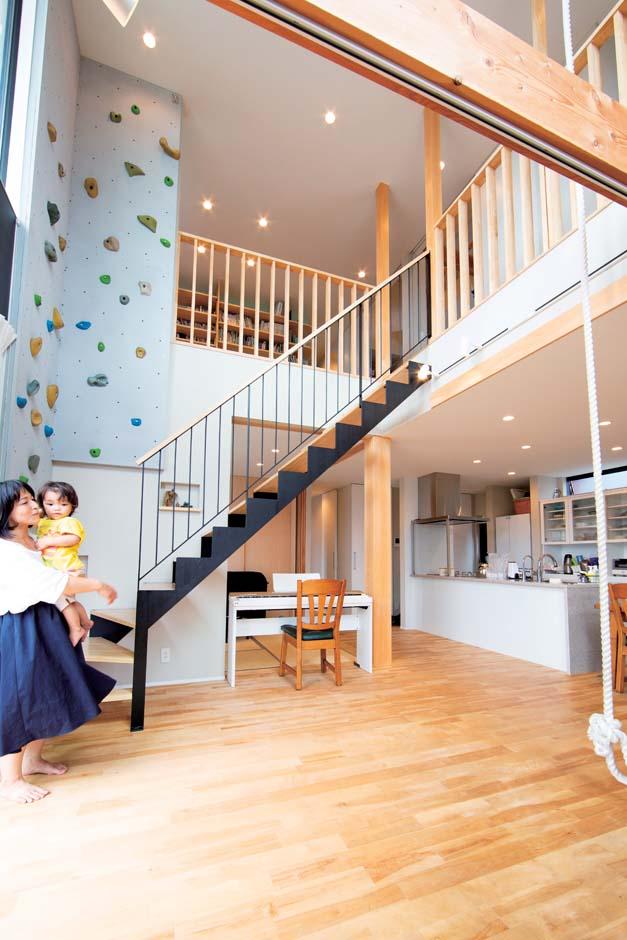 TENアーキテクツ 一級建築士事務所【子育て、間取り、建築家】ダイナミックな吹抜けのリビング。子どもたちは2階からロープで1階に降りてくる。天井まで届くボルダリングは、ご主人も筋トレに活用