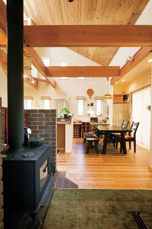 アイジースタイルハウス【デザイン住宅、自然素材、省エネ】吹抜けのLDK。天井にも無垢の杉板を貼り、ぬくもりのある空間を実現。薪ストーブは暖をとるためだけでなく、ピザや焼き芋を焼いたり、翌日の煮込み料理にも大活躍