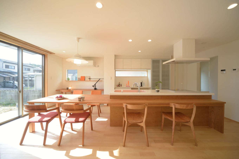 寿鉱業 ナーブの家【デザイン住宅、自然素材、間取り】大勢で腰掛けられるダイニングテーブルとカウンターを一体で製作。後ろにあるカウンターはテーブルとお揃いのブラックチェリー材。PC作業・家事・子供の勉強にと、様々な場面で活躍してくれる