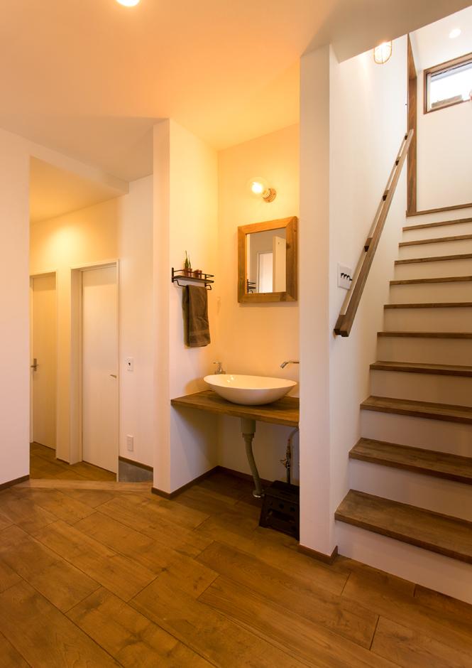 Select工房【趣味、狭小住宅、スキップフロア】帰ってきたら手を洗う癖をつけたいと、使い勝手を考えた玄関すぐの洗面コーナー。スキップダウンした奥には、家族の寝室がある