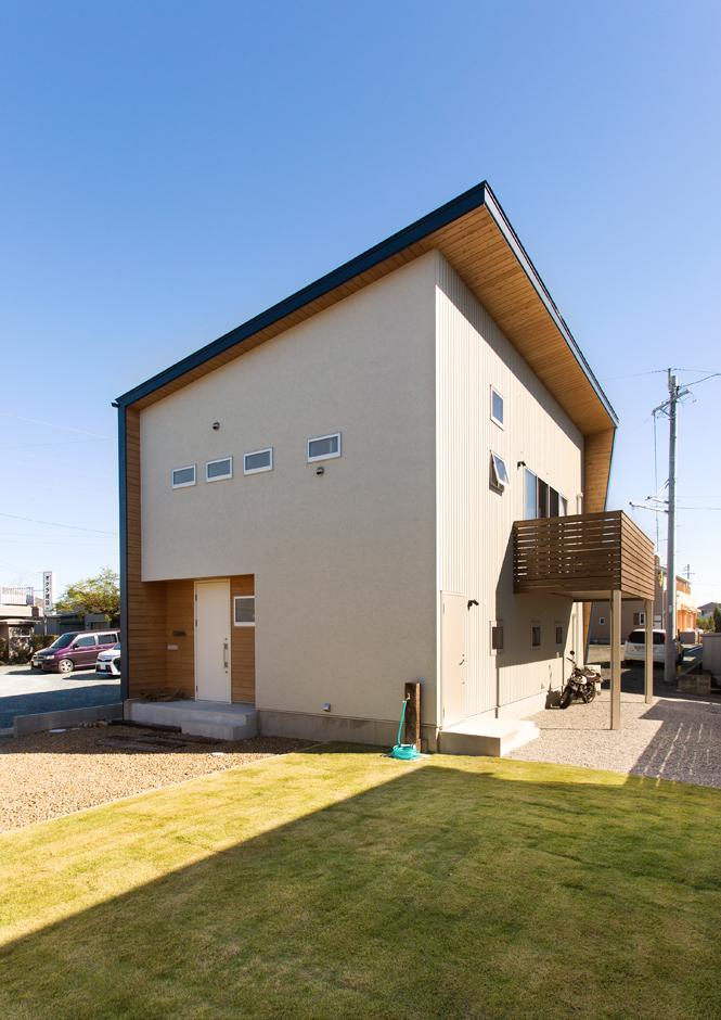 表面は塗り壁、裏面はネイビーのガリバリウム鋼板と二面性のある外壁デザインがなんとも粋。軒天井に巡らせた木が、建物のスケールに奥行きをもたらす