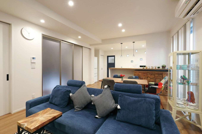 丸昇彦坂建設【デザイン住宅、間取り、収納力】22畳のLDK。大開口を開けるとパティオとつながり、より広々とした空間に。ホワイトベースな空間にダークネイビーのドアがアクセントに