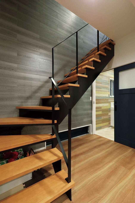 丸昇彦坂建設【デザイン住宅、間取り、収納力】オブジェのように美しい階段。木とスチールを組み合わせ、暖かみのある空間に。スケルトンにしたことで目線が抜け、開放感が生まれた。フロアタイルを壁一面に貼ってニュアンスを出した