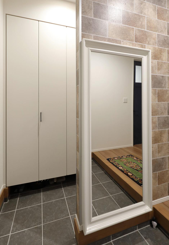 丸昇彦坂建設【デザイン住宅、間取り、収納力】家族用のシューズクローゼットと分けた玄関ホール。全身のコーディネートをチェックできる大きな鏡は空間を広く見せる効果もある。壁一面にレンガ調のエコカラットを貼ってアクセントを