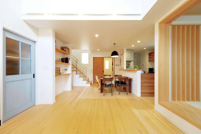 ナチュラルな雰囲気のLDKは、和室と合わせると25畳の大空間。吹抜けからたっぷりの光が降り注ぎ、明るさと開放感をもたらす。肌触りのいい床は無垢のヒノキで、冬でも素足で過ごしたくなる