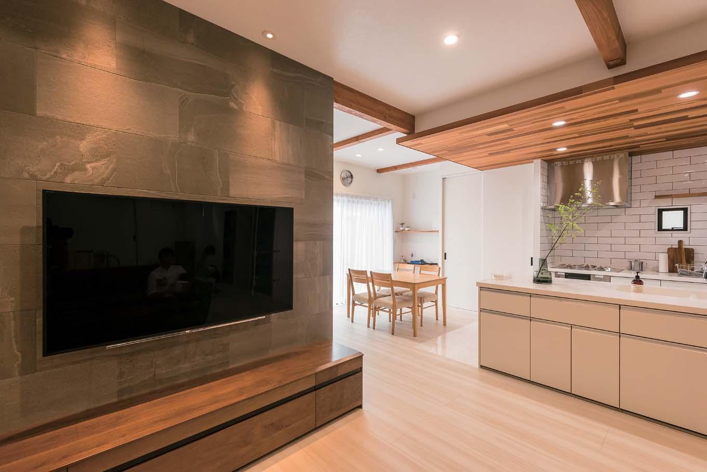 TVが掛かる壁はエコカラット。やんわりと照らすライトが上品な空間に仕上ている