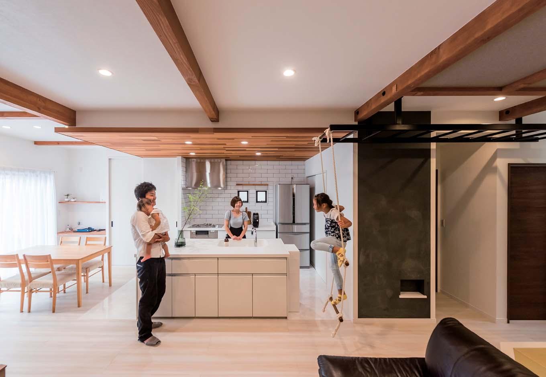 アイランドキッチンはレッドシダーの折り下げ天井。5色ある板を大工が表情豊かに組み合わせ、リビングには同色の梁を現しにし、一体感を出した