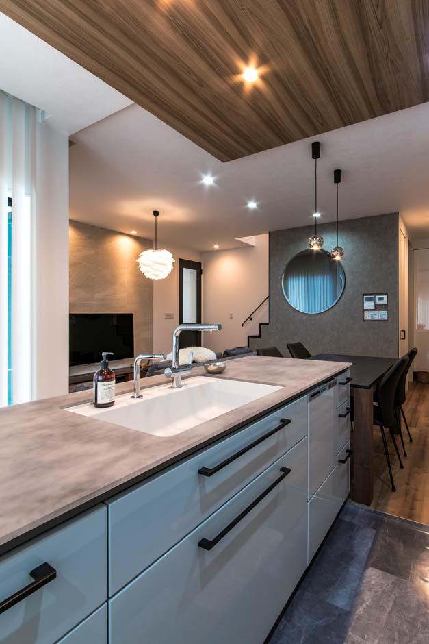 三和建設【デザイン住宅、収納力、高級住宅】憧れのアイランドキッチンは、ダイニングテーブルを横付けにして便利な配膳動線に。ダイニングの壁に付けたお気に入りのスモークの丸鏡も空間に広がりを与える