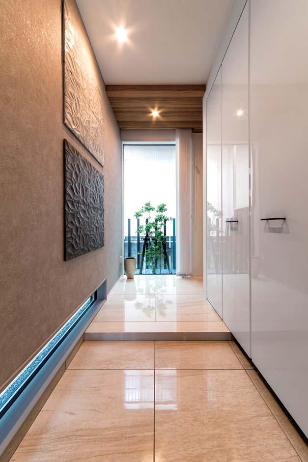 三和建設【デザイン住宅、収納力、高級住宅】色数を抑え、大理石調のパネルや段差を小さくした上がりかまちで、ホテルライクな玄関に。足元のスリット窓もポイント