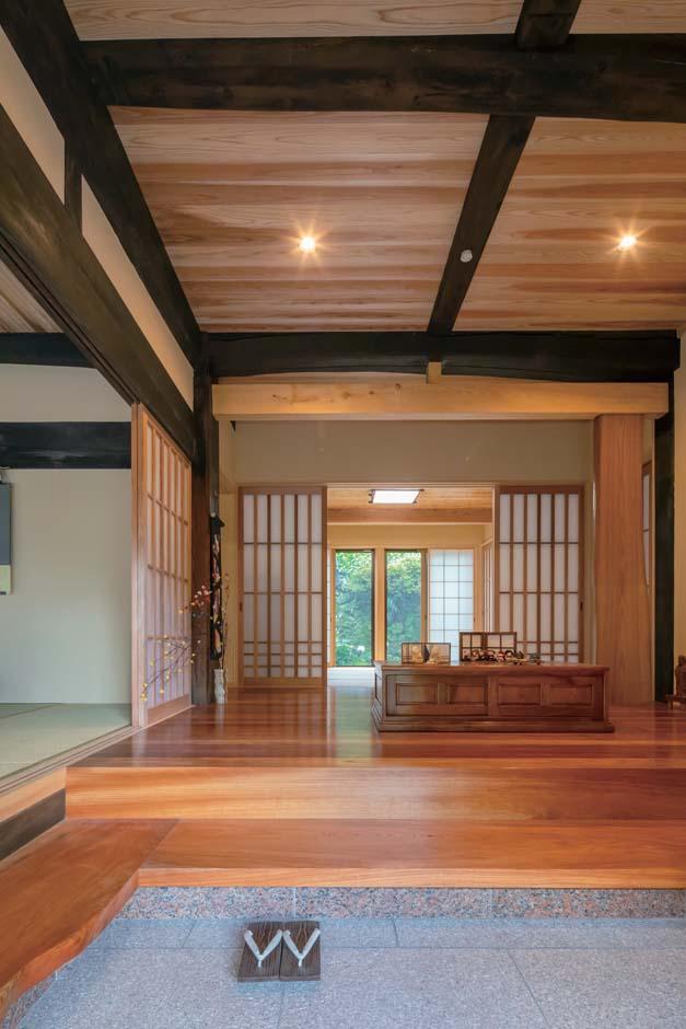 昔ながらの梁と大黒柱が、新しい材料とバランスよく融合している玄関。正面右側には存在感たっぷりのオニグルミ