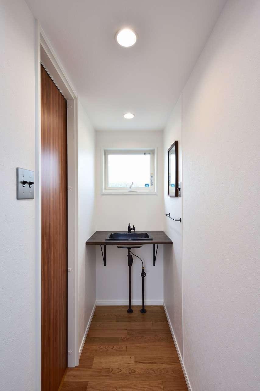 WAKO/和光地所【1000万円台、夫婦で暮らす、スキップフロア】1階の手洗いは蛇口から配管まで、Oさんが自分で選んだものを持ち込んで設置した。全体のフォルムが見えるので、インダストリアルなデザインを家具ショップで見つけてきたそう。スイッチパネルはすべてステンレス製で統一
