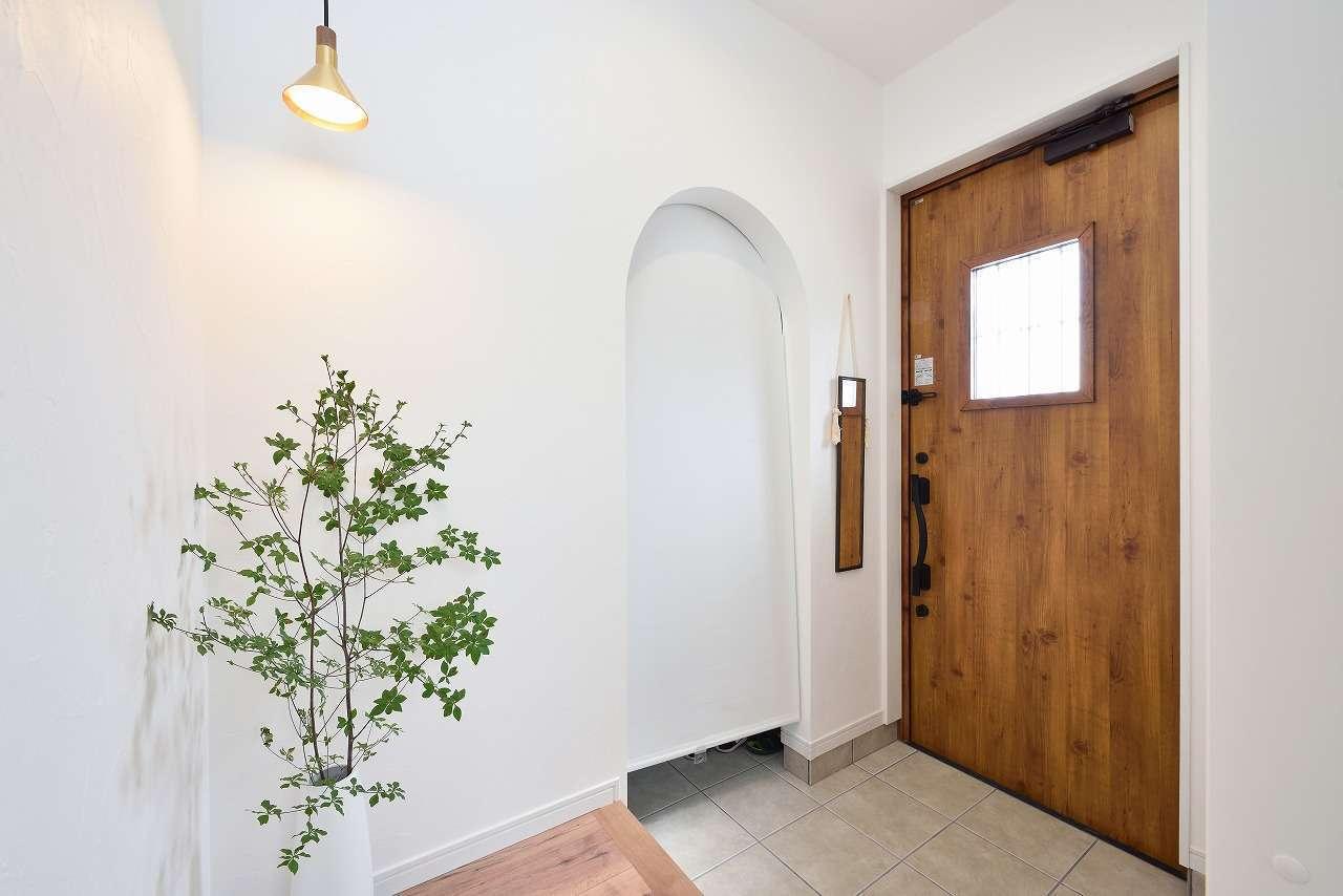 土間仕上げの玄関。アーチ状にくりぬいたファミリークローゼットは、ベビーカーやアウトドアグッズなどをすっぽり収納できて、空間を常にすっきりと保てる