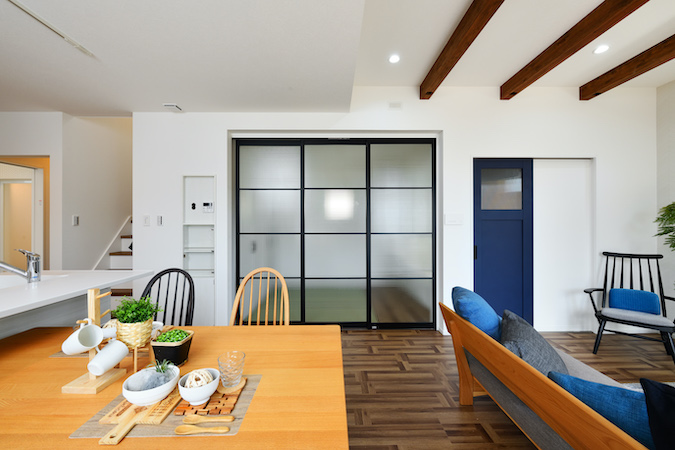 WAKO/和光地所【デザイン住宅、収納力、間取り】ネイビーの扉やダイニング横の和室に取り付けたチェッカーガラスの引き戸が空間のアクセントとなり、デザイン性の高い空間を演出