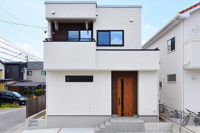 WAKO/和光地所【デザイン住宅、収納力、間取り】「木目をどこかしらには入れたい」という要望から、玄関ドアに木目を採用。外観の色は悩んだすえに木目と相性の良い白の外壁にした