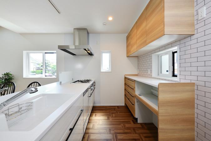 WAKO/和光地所【デザイン住宅、収納力、間取り】白を基調とした空間に、木目やタイルといったアクセントが光るキッチン。随所に溢れるセンスの良さが空間をより明るく彩る