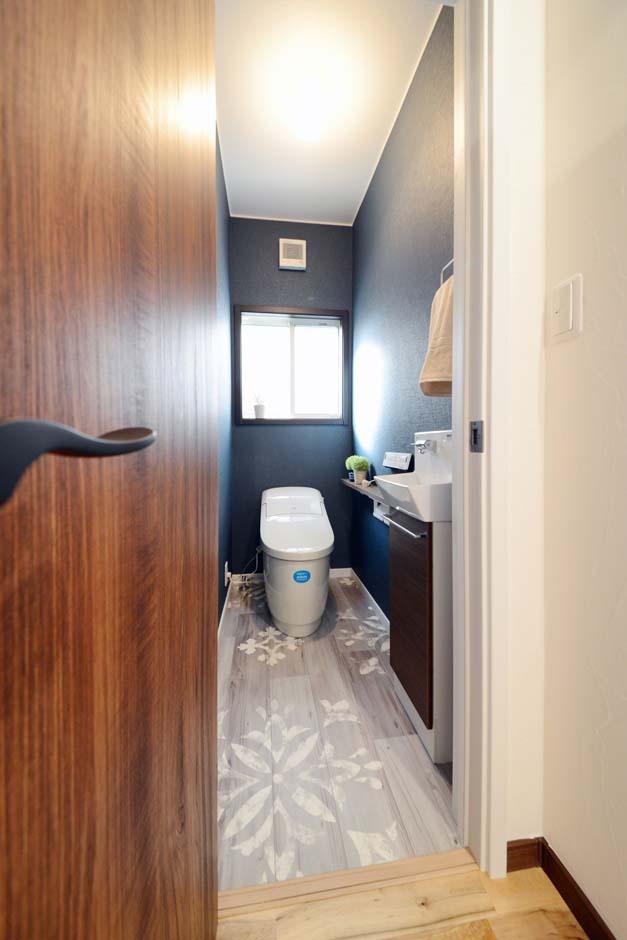 静鉄ホームズ【コアハウス】【1000万円台、趣味、インテリア】ネイビーのクロスと濃い目の木目で、落ち着きある雰囲気に統一された1階のトイレ。タンクレスの便器にあわせ、コンパクトな手洗器を設置した。