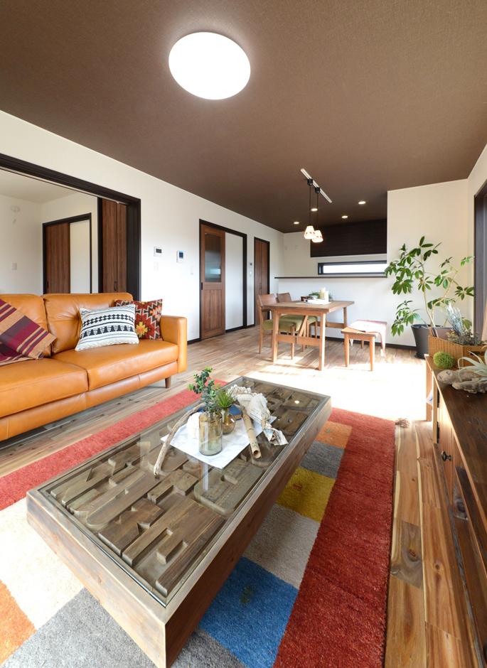 静鉄ホームズ【コアハウス】【1000万円台、自然素材、インテリア】無垢の床、塗り壁、ヴィンテージ調の建具に天井をアクセントクロスで仕上げたリビングダイニング。アジアンリゾートをイメージさせる家具や小物でまとめた施主さんのセンスの良さを感じさせる空間だ。