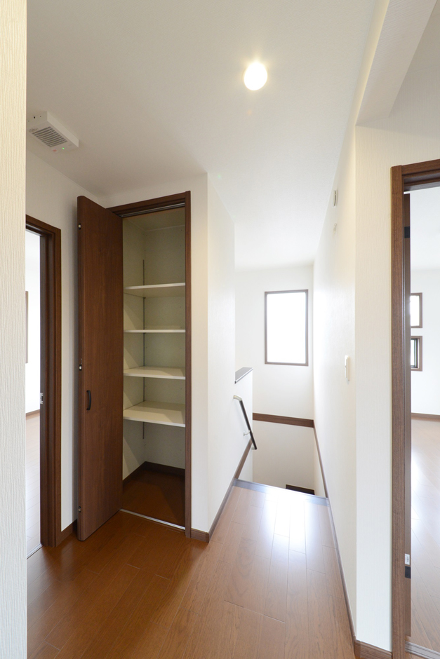 静鉄ホームズ【コアハウス】【1000万円台、自然素材、インテリア】2階ホールにはみんなで使える収納スペースを設置。決められたプランの中からご家族のライフスタイルにぴったりの間取りを選んでいくコアハウスの家づくりだが、収納を増やしたりカウンターをつけたりなど、カスタマイズは無限大。