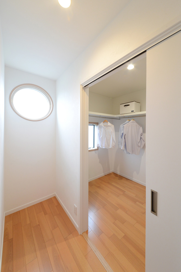 M様邸のアイキャッチポイントでもある丸窓が覗く廊下。独立したウォークインクローゼットは家族誰でも使用することができ、みんなの衣裳部屋としても活躍してくれそう。