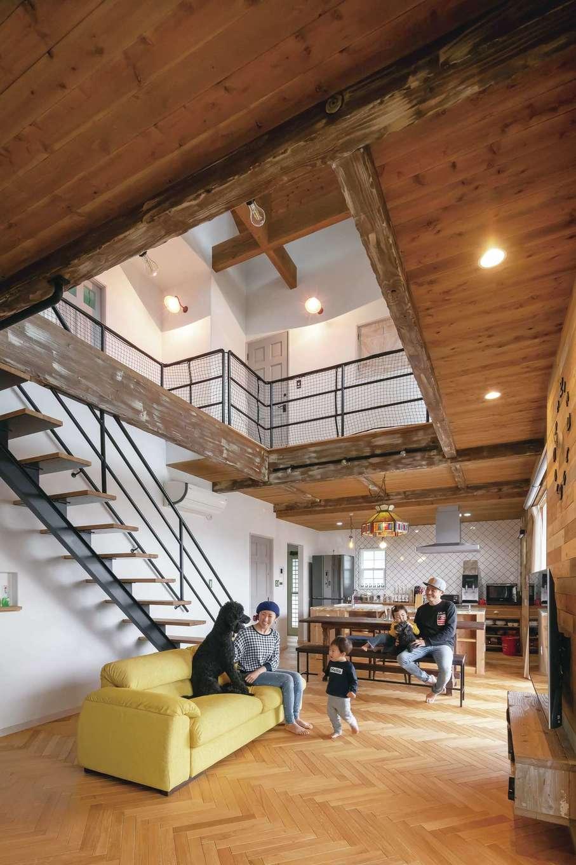 富士ホームズデザイン【子育て、自然素材、インテリア】ヘリンボーンの床とアンティーク家具で男前な空間にコーディネートした吹抜けのLDK。無垢オークの床、珪藻土の壁、スチールの階段がバランス良く調和したことで、人も愛犬もリラックスして過ごすことができる