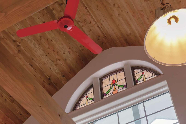 富士ホームズデザイン【子育て、自然素材、インテリア】「なければ、作っちゃえばいいじゃん!」が上総さんの建築美学。ファンを赤くペイントし、高い吹抜けの窓にアンティークのステンドグラスをはめ込んで、夫妻のイメージをカタチにした