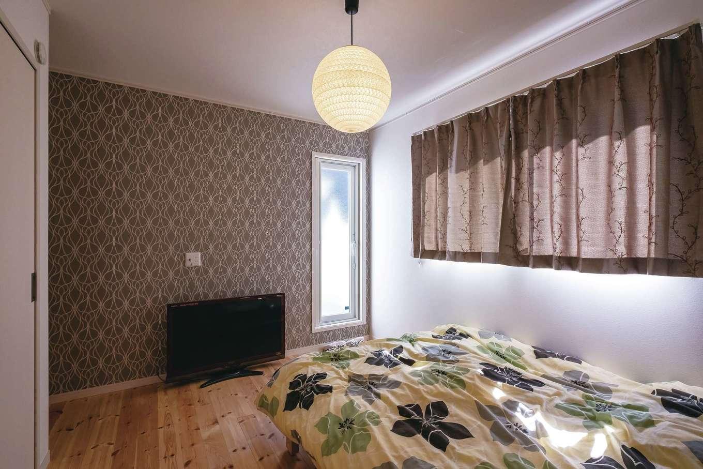 寝室は壁の一面だけブラウン系のクロスを採用し、落ち着きを演出。照明やカーテンも、雰囲気に合うものを選択した。奥の扉はベランダに続く