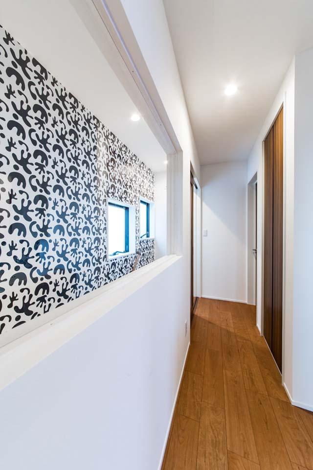 小玉建設【デザイン住宅、子育て、省エネ】階段側の壁にモノトーンのモダンなクロスをチョイス。ホールの窓がアート作品のよう