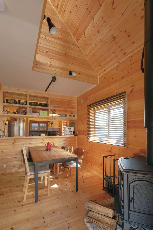 標準仕様とは違う位置に吹き抜けを設計し、薪ストーブを置いたダイニング。キッチンの造作収納や、あえてデザインの違うチェアを並べたテーブルがおしゃれ