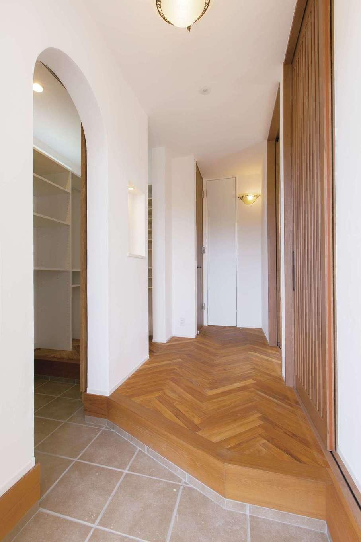 コバケンホーム(小林建設)【収納力、自然素材、間取り】ヘリンボーンの無垢の床とシューズクロークのRの壁が優雅な雰囲気を醸し出す玄関。ヘリンボーンは夫妻のこだわりでオプションとして採用したもの