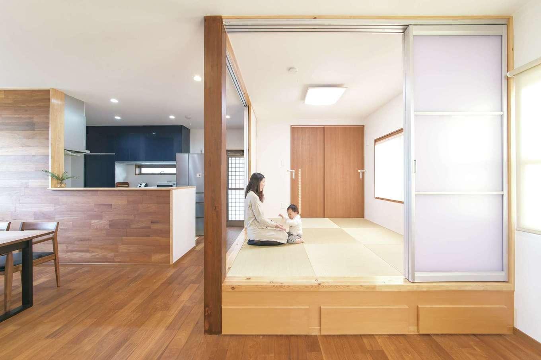 釜慶鉄工【趣味、ガレージ、鉄骨鉄筋コンクリート構造】重量鉄骨ならではの大空間・大開口を実現したLDK。チークの床が温かみと高級感をもたらしている。壁にはエコカラットを使用。室内の湿気を吸収すると同時に空間のアクセントとしても役立っている。リビングの背面には小上がりがある