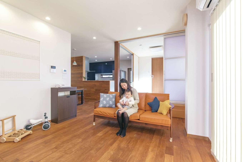 釜慶鉄工【趣味、ガレージ、鉄骨鉄筋コンクリート構造】重量鉄骨ならではの大空間・大開口を実現したLDK。チークの床が温かみと高級感をもたらしている。壁にはエコカラットを使用。室内の湿気を吸収し、空間のアクセントとしても活躍