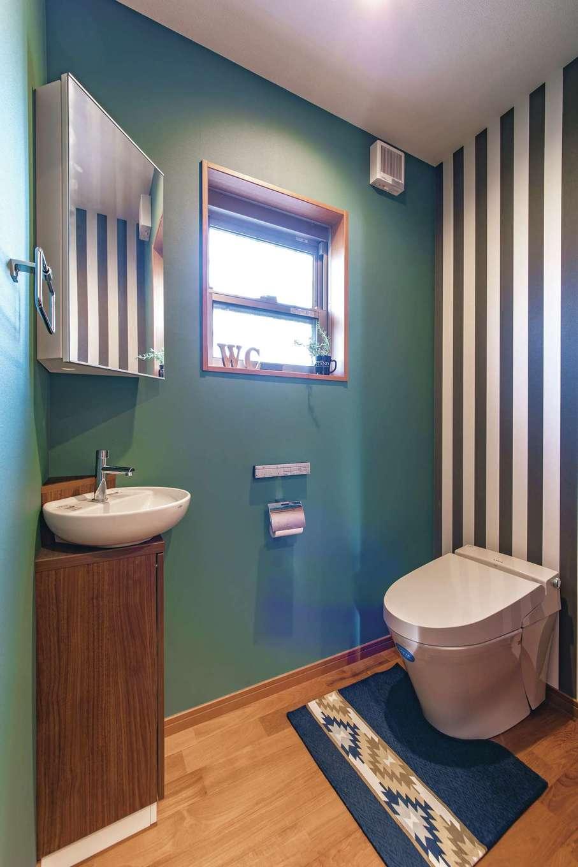 釜慶鉄工【趣味、ガレージ、鉄骨鉄筋コンクリート構造】玄関の奥に設けたトイレ。床は廊下と同じチークの無垢材。手洗いを斜めに設け、クロスのコーディネートでオシャレに演出
