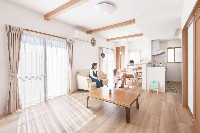 Um House(マル祐戸田建築)【子育て、収納力、間取り】南に面した明るいLDK。ダークブラウンの床、白い壁に現しの梁がアクセントに。冷蔵庫や調理家電を見せず、生活感を出さない