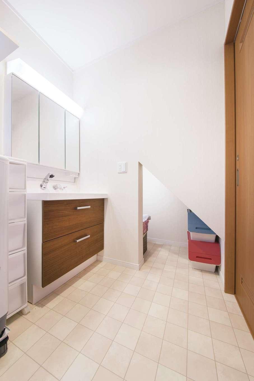 Um House(マル祐戸田建築)【子育て、収納力、間取り】キッチンから近い場所にある洗面脱衣室。階段下を利用したこぢんまりとした収納スペースは、子どもの絶好の遊び場にもなっている