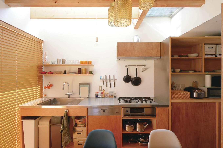 MABUCHI【デザイン住宅、狭小住宅、間取り】ラワン材で仕上げたオーダーメイド・キッチン。オープンラックを壁に設け、「見せる収納」を上手にとり入れている。キッチン部分も吹抜けになっているため、大きな高窓から光が注ぎ、清々しい気分で調理ができる