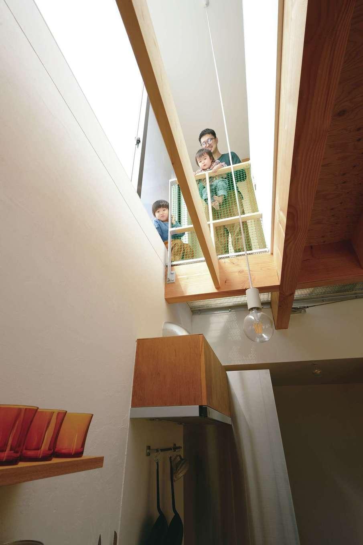 MABUCHI【デザイン住宅、狭小住宅、間取り】キッチンは吹抜けを通じて2階と繋がっている。「おーい、ママ」とお子さまが奥さまに声をかけたりと、常に家族が一体感を味わえる