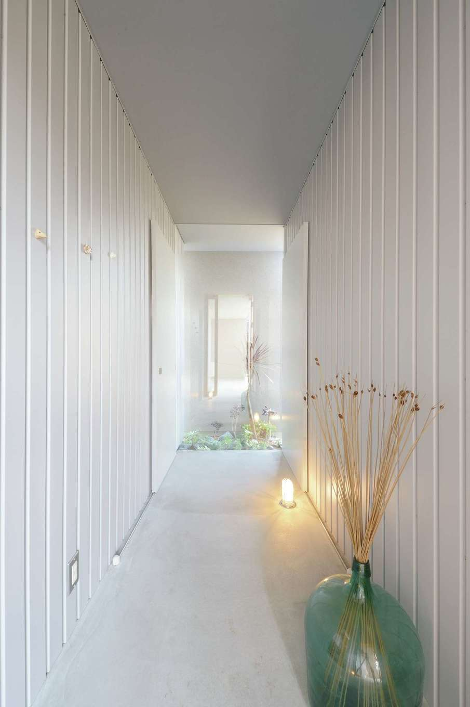 MABUCHI【デザイン住宅、狭小住宅、間取り】玄関の土間の奥はガラス張りになっている。無機質な空間に坪庭のグリーンが映えて美しい