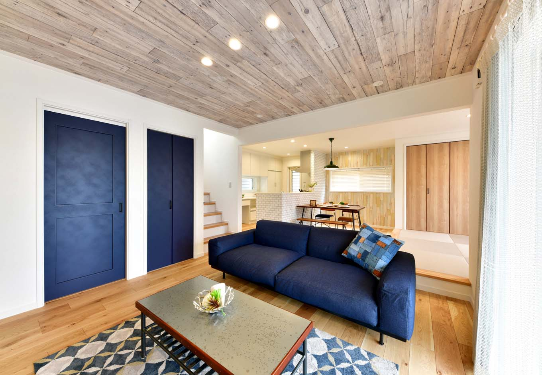 ヴィンテージ加工されたブルーの建具がポイントとなり、木のぬくもりを感じるリビング空間。天井で使用している古木調のクロスも海岸沿いの暮らしをイメージしている。
